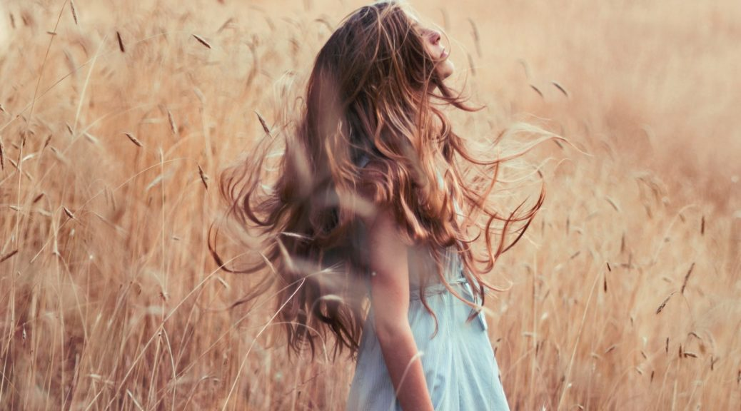 a-beautiful-girl-with-very-curl-long-hair-standing-on-the-reed-field